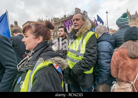 London, UK. 15th January 2019. Yellow-jacketed protesters at College Green. Groups against leaving the EU, including SODEM, Movement for Justice and In Limbo and Brexiteers Leave Means Leave and others protest opposite Parliament as Theresa May's Brexit deal was being debated.  While the two groups mainly kept apart, a small group, some in yellow jackets came to shout insults at pro-EU campaigners, while police tried to keep the two groups separate. Credit: Peter Marshall/Alamy Live News - Stock Image