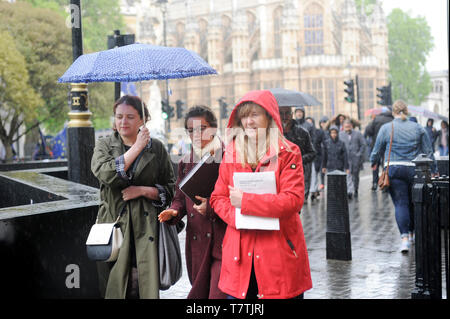 London, UK. 09th May, 2019.  Walking outside the Houses of Parliament in the rain. Rain in London West End. Credit: JOHNNY ARMSTEAD/Alamy Live News - Stock Image