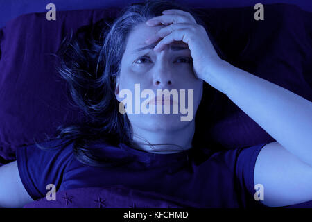 Middle aged woman lying awake in her bed at night because of insomnia, stress, fears, nightmares or illnesses like - Stock Image