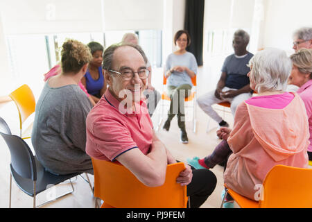 Portrait happy active senior man meeting with group in circle in community center - Stock Image