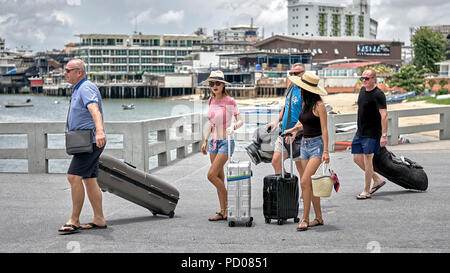 Thailand tourists. Western men on a Thai golfing holiday with golf equipment and Thai girl companions. - Stock Image