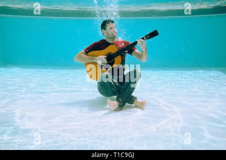 Young Man Playing Music With Guitar And Singing Song Underwater - Stock Image