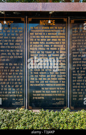 Notice explaining the 1919 Jallianwala Bagh Massacre shooting at the entrance to Jallianwala Bagh, a public commemorative garden, Amritsar, Punjab, India - Stock Image