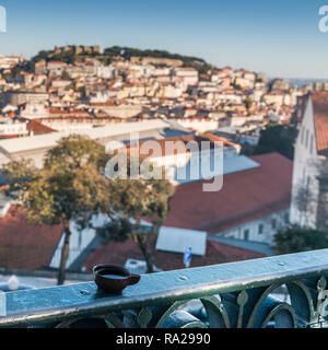 Ginja de Obidos, traditional sour cherry liquor, served in small cups made of chocolate with Lisbon panorama background - Stock Image