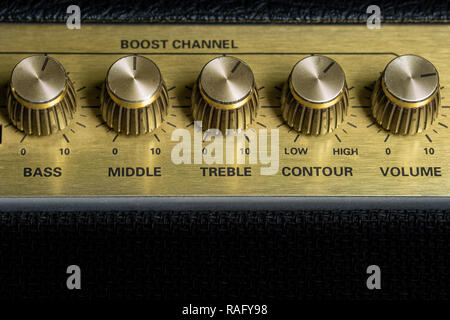 vintage amplifier five knobs horizontal closeup, music recording studio equipment, bottom copy space - Stock Image