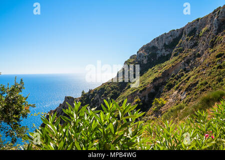 Beautiful summer panoramic seascape. View of the coastline into the sea bays with crystal clear azure water. In the backlight sunbeam light. Paleokastrica. Corfu. Ionian archipelago. Greece. - Stock Image