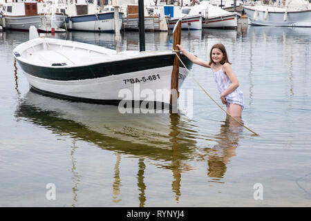 Young girl pushing a rowing boat in shallow waters in the sea at Palamos in Spain - Stock Image