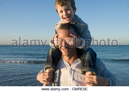 Boy on fathers shoulders by the sea - Stock Image