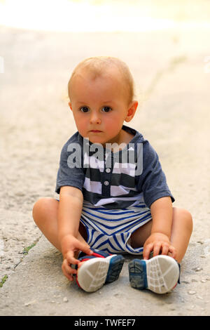Cute Baby Boy Sitting On The Floor In The Street, Close Up Portrait - Stock Image