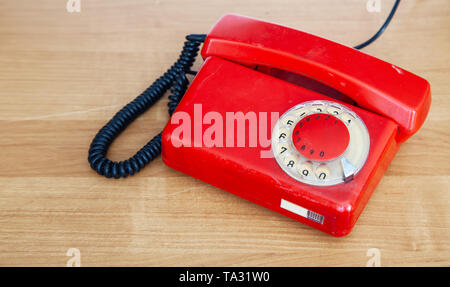 red retro phone on the table indoor closeup - Stock Image