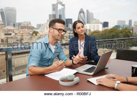 Businesspeople during meeting on balcony - Stock Image