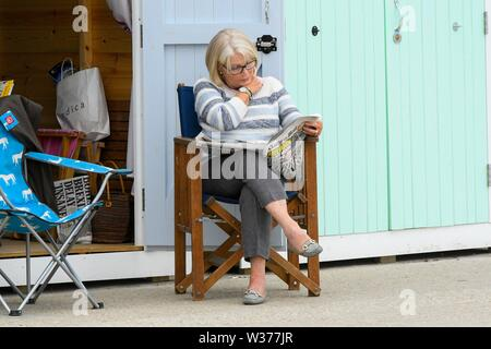 Lyme Regis, Dorset, UK.  13th July 2019. UK Weather.  A woman reading a newspaper outside a seafront beach hut at the seaside resort of Lyme Regis in Dorset on a warm cloudy day.  Picture Credit: Graham Hunt/Alamy Live News - Stock Image