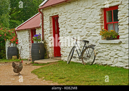 Bicycle leaning against a white walled cottage - Stock Image