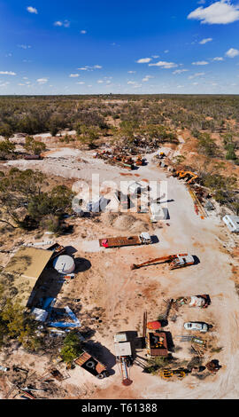 Cemetery of old abandoned rusty trucks and mine machinery in Lightning Ridge opal mining town in Australian outback seen from above on a hot sunny day - Stock Image
