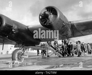 Passengers board a Lufthansa Focke-Wulf FW 200 'Condor' aircraft at Berlin-Rangsdorf Airport. In the background, a Junkers Ju 52 of the Danish airline DAL. - Stock Image