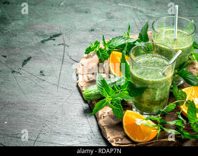 Green smoothie with vegetables, fruits and mint. On rustic background. - Stock Image