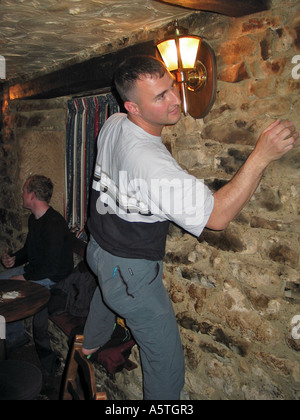 Young man indoor climbing the walls in an Inn after a few beers during a stag party weekend - Stock Image