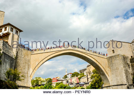 A local Bosnian prepares to jump off the Stari Most, the old bridge in Old Town Mostar, Bosnia and Herzegovina as tourists gather to watch the event - Stock Image