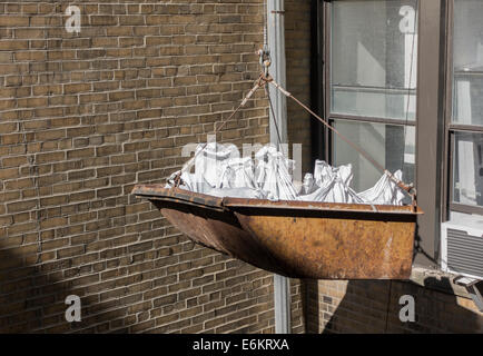 construction bucket being lowered with bags of debris - Stock Image