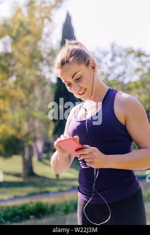 vertical photo of an attractive blonde sports woman listening music while preparing for run outdoors at park, fitness accessories - Stock Image