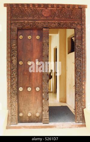 Ornate Swahili carved wooden door in Lamu, Kenya - Stock Image