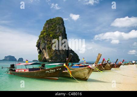 Thailand, Krabi, Railay. Longtail boats at Hat Phra Nang (Phra Nang Beach) with Happy Island in the background. - Stock Image