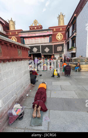 Tibetan Buddhist monk performing prostration in front of Jokhang temple, Lhasa Tibet - Stock Image