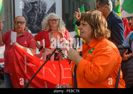 London, UK. 13th August 2018.  One of the event organisers begins the Brazilian protest outside the Brazilian embassy calling for the release of Luiz Inacio Lula da Silva, a former trade union leader who was President of Brazil from 2003-11 to enable him to stand for election again in October. Credit: Peter Marshall/Alamy Live News - Stock Image