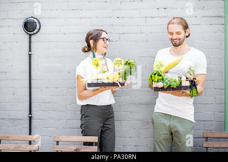 Young vegetarian couple standing with boxes full of fresh vegetables outdoors on the gray wall background - Stock Image