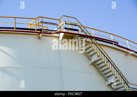 White oil or chemical tanks with spiral staircase.Stairs to the top of an oil or chemical tank .Staircase on big fuel tank - Stock Image