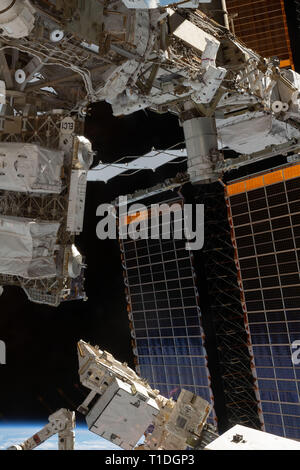 Expedition 59 NASA astronaut Anne McClain, top, works on the power system during a spacewalk outside the International Space Station March 22, 2019 in Earth Orbit. Astronauts McClain and Hague spent six-hours and 39-minutes outside the space station to upgrade the orbital complex's power storage capacity. - Stock Image