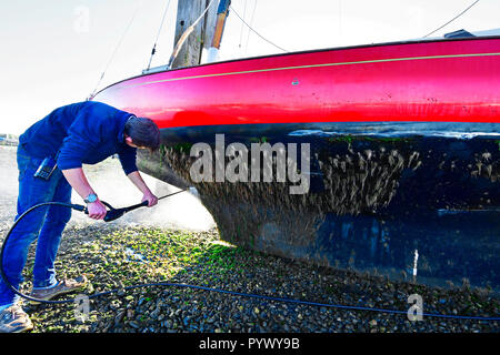 Man pressure hosing excessive algea weed growth off the hull of his X boat,Madame x )  as it rests against Itchenor's scrubbing off Dolphins - Stock Image