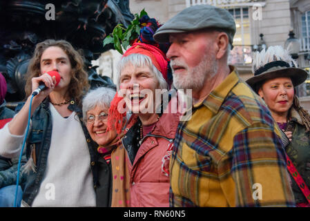 London, UK. 16 February 2019. Venus CuMara with some of the veteran attenders. The 16th 'Reclaim Love' free Valentine's Day street party takes place around the statue of Eros in Piccadilly Circus, with drumming, music, dancing poetry to celebrate love. The event, which was founded by poet Venus CuMara, aims to reclaim love as a manifestation of the human spirit from the sleazy commercialisation which has taken over Valentine's Day as a festival of profit. Credit: Peter Marshall/Alamy Live News - Stock Image