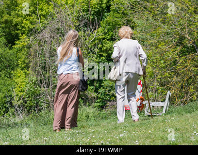Pair of women who may or may not be Mother and Daughter looking from behind walking on a warm day in the countryside in Spring in the UK. - Stock Image