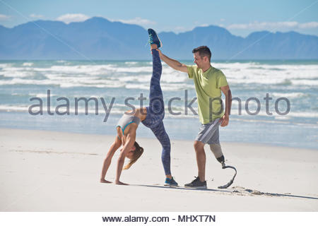Man Wearing Prosthetic Blade Helping Woman In Gymnastic Pose On Beach - Stock Image