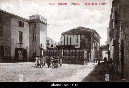 Plaza de la Victoria, in the town of Alcudia, Majorca, Spain, with children holding hands in a circle.      Date: circa 1910 - Stock Image