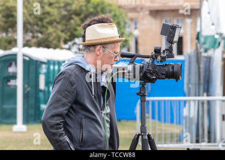 A camera man setting up his camera to film an outdoor event - Stock Image