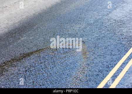 Water from a burst water main coming up through a manhole cover in the middle of the road - Stock Image
