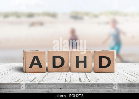 ADHD sign on a wooden table with kids acting wild in the background - Stock Image