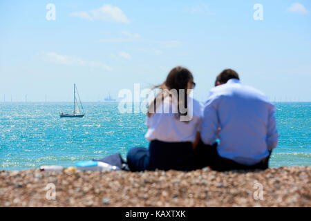 A couple enjoys the sun in Brighton, with sail in focus in the background. - Stock Image