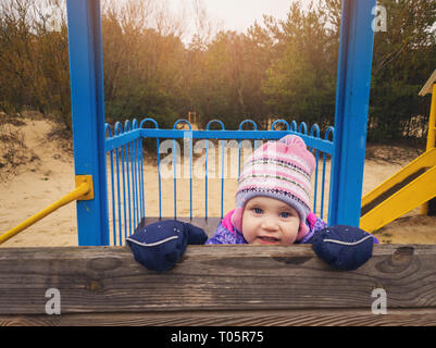 playful happy little girl at playground on sunny spring day - Stock Image