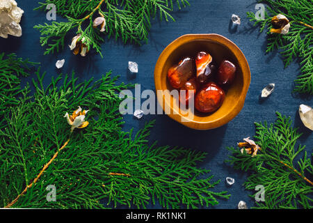 Carnelian and Quartz Points with Incense Cedar on Blue Stained Wood - Stock Image