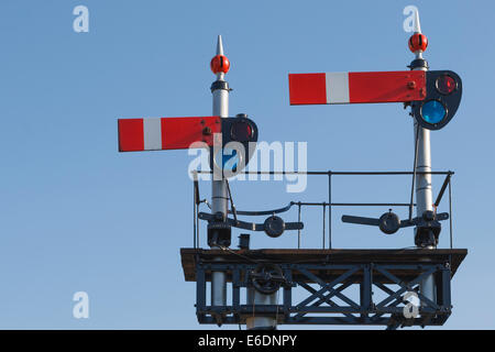 Vintage British train signal in the stop position on the West Somerset Railway, against clear blue sky. - Stock Image