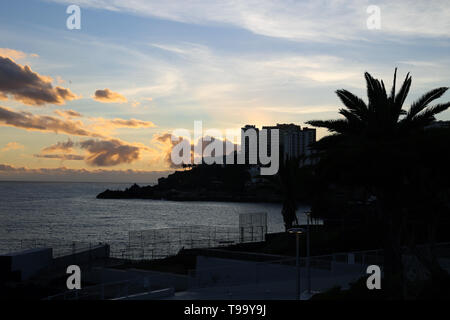 Colorful landscape with a stunning sunset located in Funchal, Madeira. The sky is colored with orange, gold and blue. Beautiful! - Stock Image