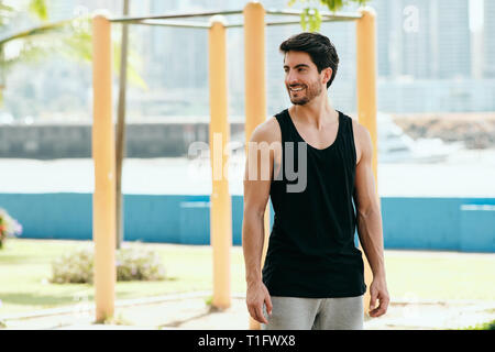 Beautiful young man training and working out in park. Handsome hispanic athlete standing and looking at camera after fitness routine. Portrait of Lati - Stock Image