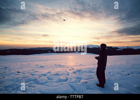 Man flying drone in sky while standing on snowy mountains - Stock Image