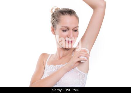 Beautiful woman putting antiperspirant stick deodorant in underarms - Stock Image