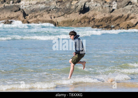 An excited teenage holidaymaker running into the sea at Fistral in Newquay in Cornwall. - Stock Image