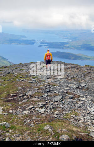 Walker descending Ben More on Mull with views of Loch Na Keal with the island of Eorsa and beyond the narrows between Ulva on the left and Mull - Stock Image