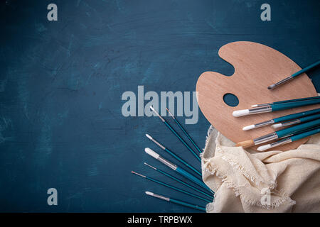 Wooden art palette and paint brushes on blue background, copy space, flat lay - Stock Image